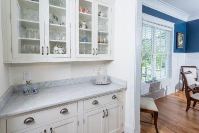 butlers pantry built of white shaker inset cabinets flows through to dining room with deep blue painted walls above painted white board and batten paneling and cherry upholstered dining chairs