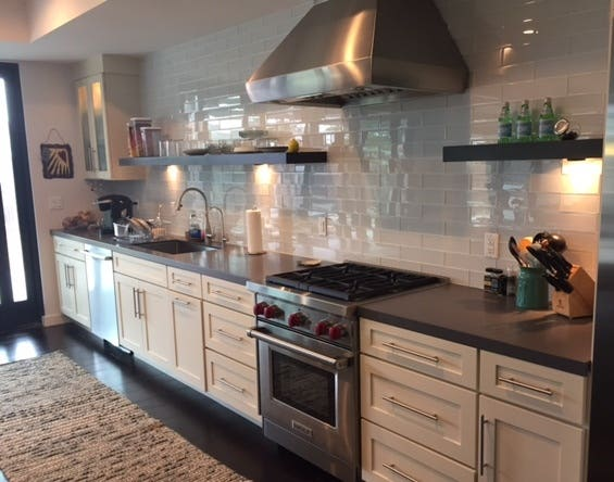 long kitchen wall with white shaker base cabinets, white subway tile wall, open shelves and one glass-door cabinet