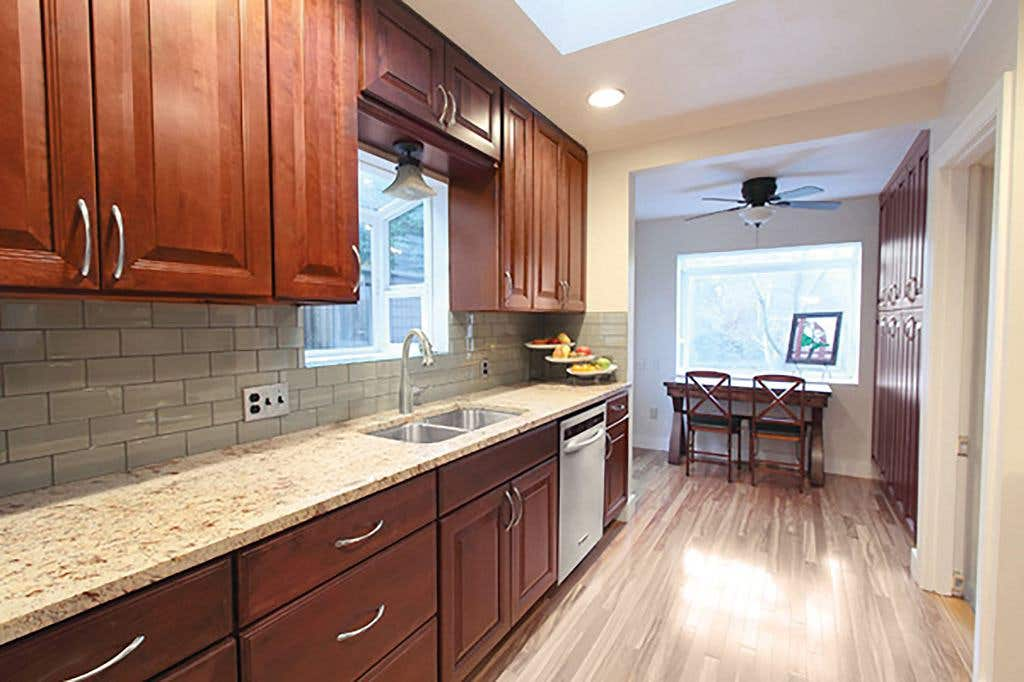 kitchen has raised-panel cherry cabinets, hardwood floors, bay window over the sink, skylight and picture window in the eating nook with pantry
