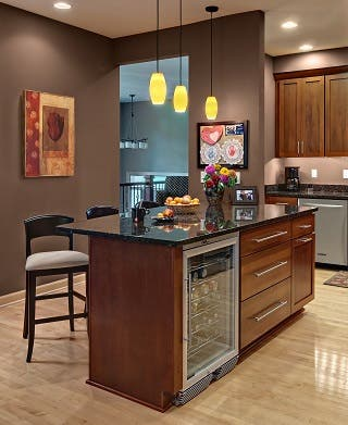 cherry kitchen island with black granite countertop and under-counter beverage cooler