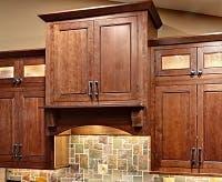 cherry glass-door cabinets bordering custom wood range hood. Hood projects forward for visual interest