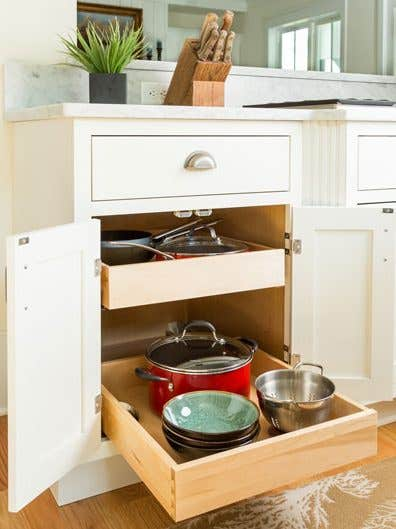Double roll-out trays storing bowls, pots, and a colander. Featuring an White inset styled base cabinet