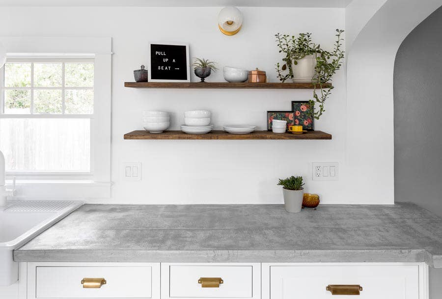 open wood kitchen shelving above concrete countertops and white inset cabinets with gold hardware