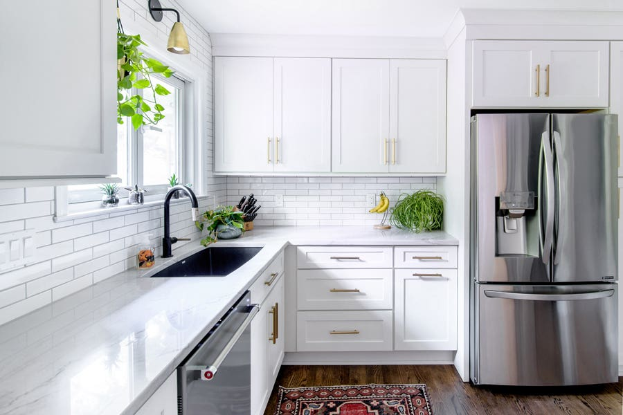A kitchen using CliqStudios Dayton cabinets in White, with stainless steel appliances and green plant accent pieces.