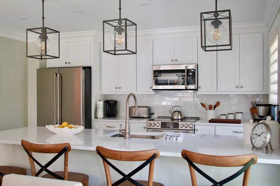 Kitchen with white shaker cabinets, black metal fixtures, stainless appliances and wood chairs on peninsula