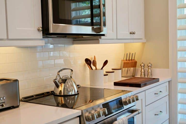 Stainless steel stove and microwave surrounded by white shaker cabinets, subway tile backsplash and white countertops