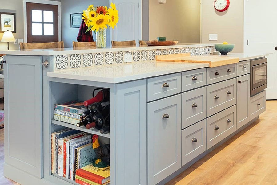Large Harbor color two-tier island with white countertops and blue tile backsplash and farmhouse hardware cup pulls