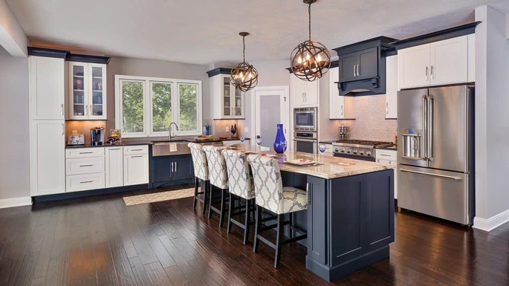 Beautifully designed open floor plan kitchen features painted shaker style cabinetry by CliqStudios. Shown Dayton shaker cabinet style in painted White finish and paired with Dayton in painted Carbon finish.