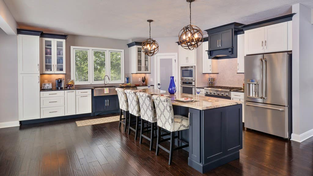 Open kitchen seen from living area has large black island with seating for four, ball pendant island lighting, wood range hood over gas cooktop, and glass door display cabinets next to sink window.
