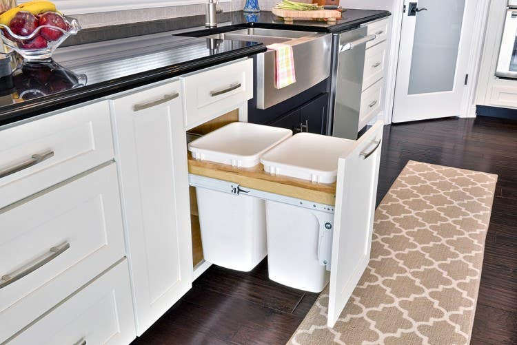 Smart storage solutions by CliqStudios keeps your kitchen organized with features such as this base cabinet with convenient double bins for trash and recycling, shown here in Dayton shaker cabinet style in painted White finish.