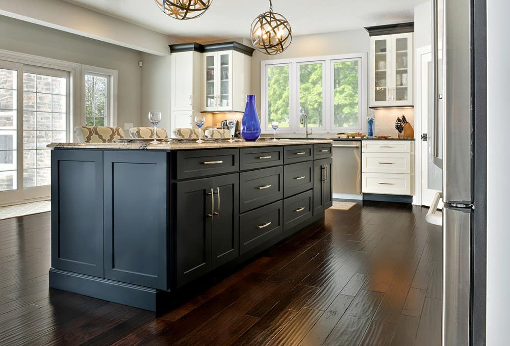 Open kitchen design in modern transitional style has large black island cabinets, black crown molding on white Shaker perimeter cabinets, and distressed hardwood flooring.