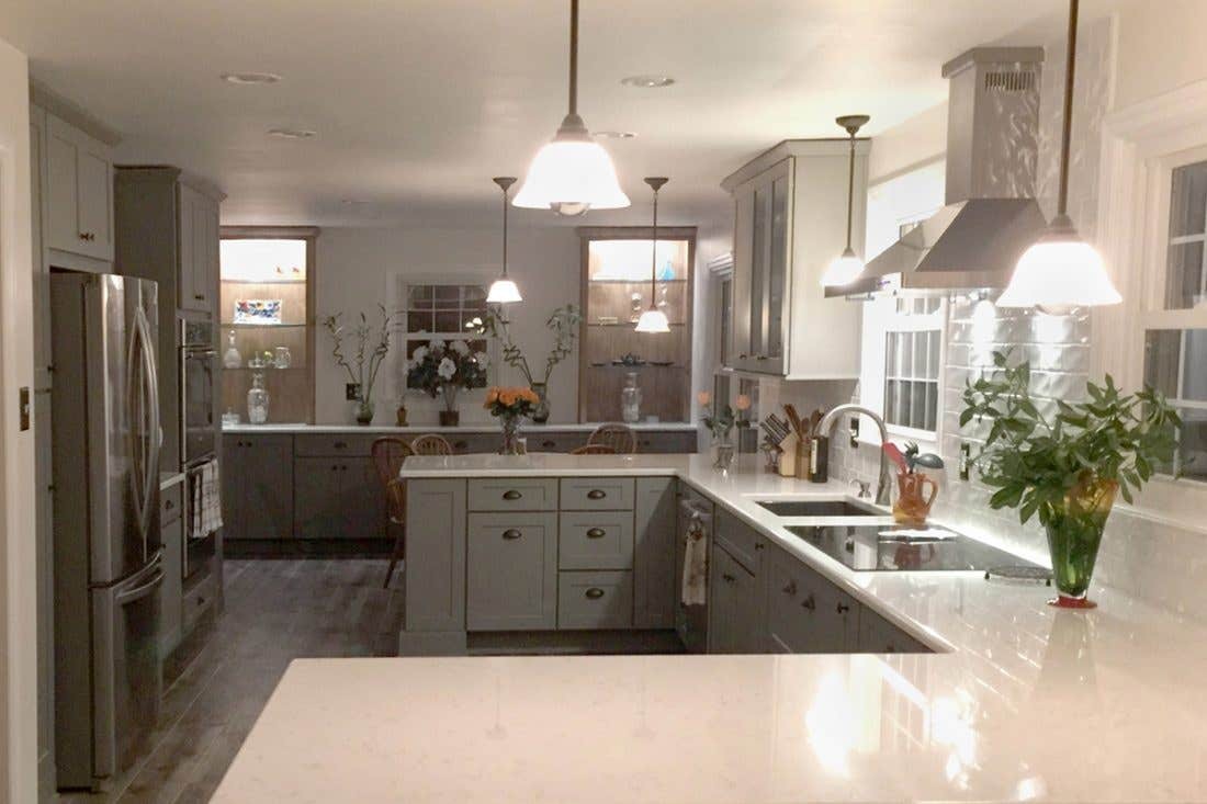 Gray kitchen with two peninsulas, stainless appliances, dining room buffet and beverage center