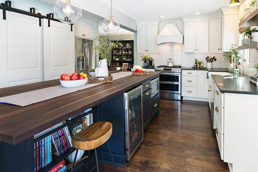 A black island with butcher block counter tops and a built in microwave, bookshelf, and cooler.
