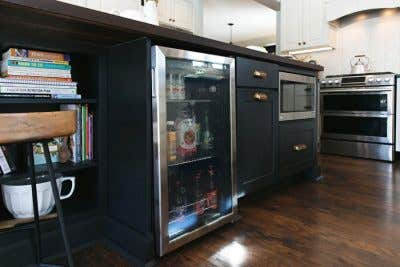 Black kitchen island base with open shelves, a built in microwave, and a built in cooler.