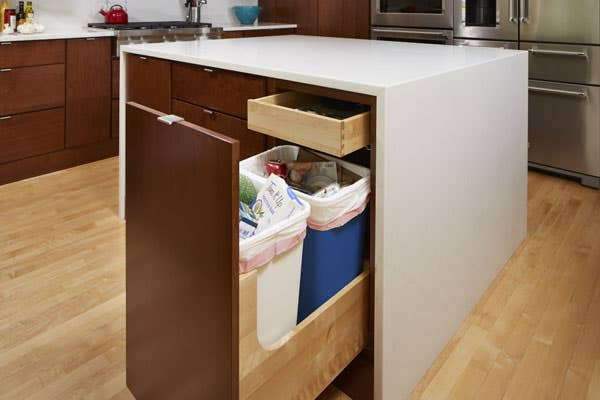 A Wastebasket cabinet in CliqStudios Studio 31 style in Cider finish containing a full trash can and full recycling bin.
