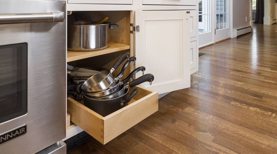 Lower roll-out tray in a base cabinet storing stacked pots. and pans.