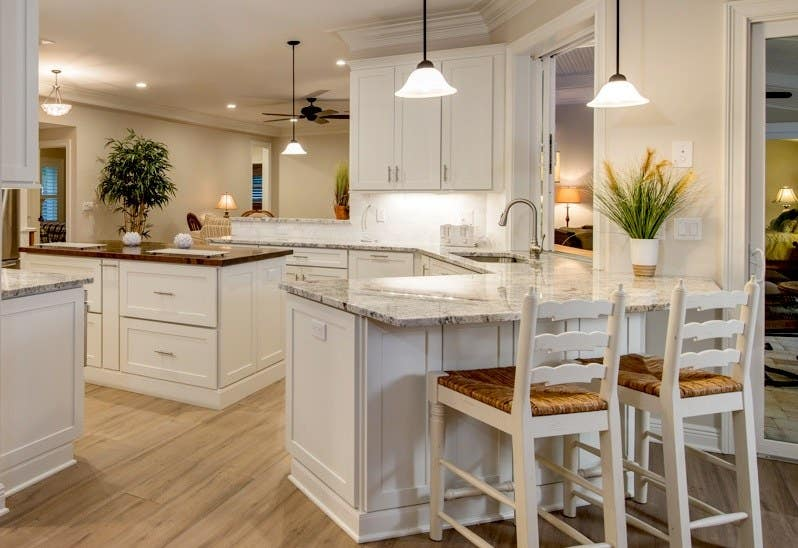kitchen with white shaker cabinets has center island with butcher block countertop, peninsula with rattan bar stools, potted plants on counters and hardwood floors
