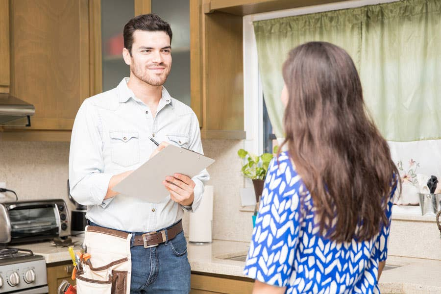 contractor standing in front of outdated kitchen cabinets presenting remodeling options to a homeowner