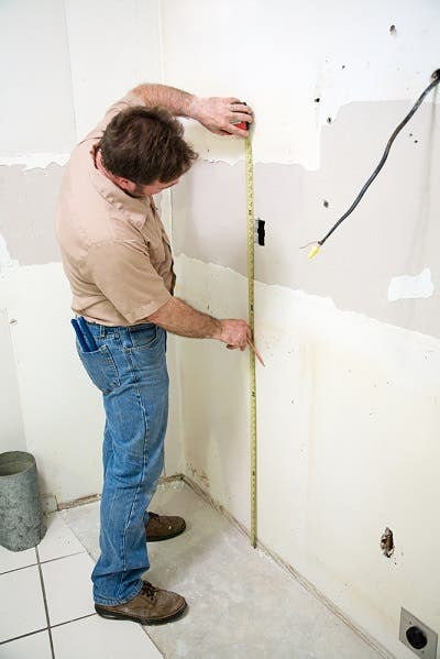 contractor measuring wallboard in kitchen remodel
