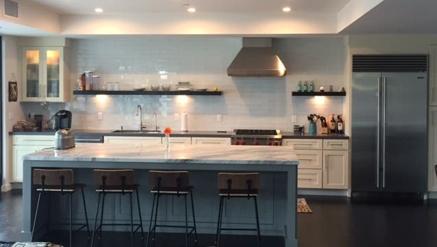 contemporary kitchen with white shaker base cabinets, open shelves and glass-door cabinet on wall, and furniture-look center island
