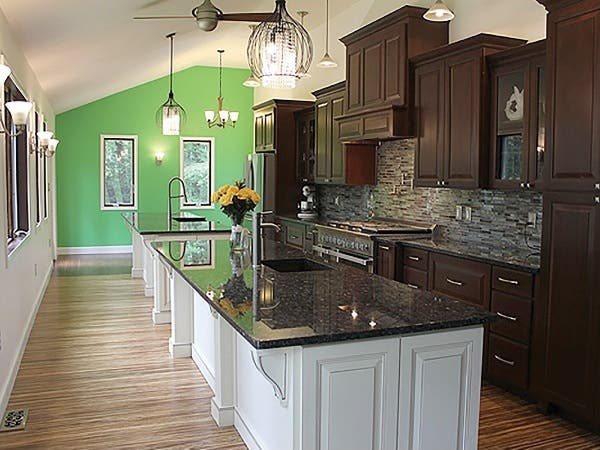 A wall of dark cherry cabinets with raised-panel doors faces two white kitchen islands and a bank of windows