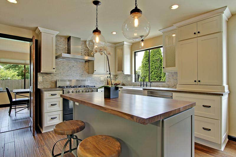 kitchen with white and gray painted cabinets, butcher block countertop on the island and clear glass pendant lights