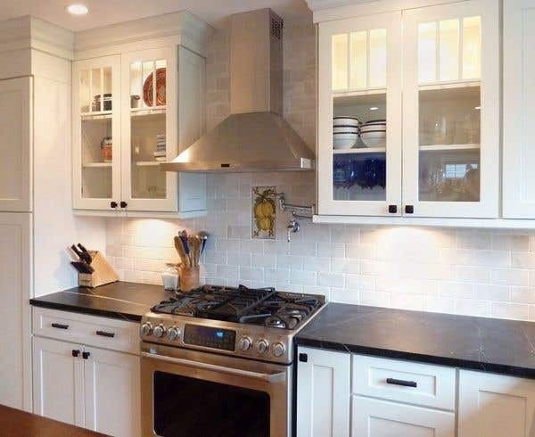 kitchen with glass door cabinets on either side of professional stainless range hood with under-cabinet lights, white shaker cabinets and black granite countertops