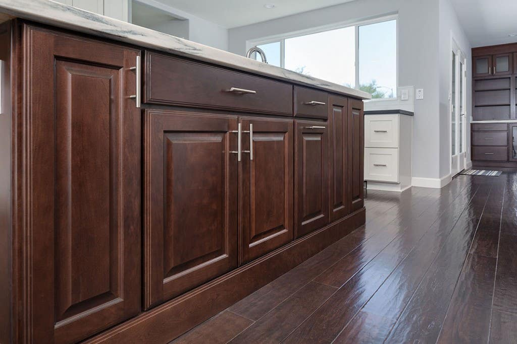 cherry cabinets with raised panel doors are used to build a kitchen center island trimmed with ogee toekick for a furniture look