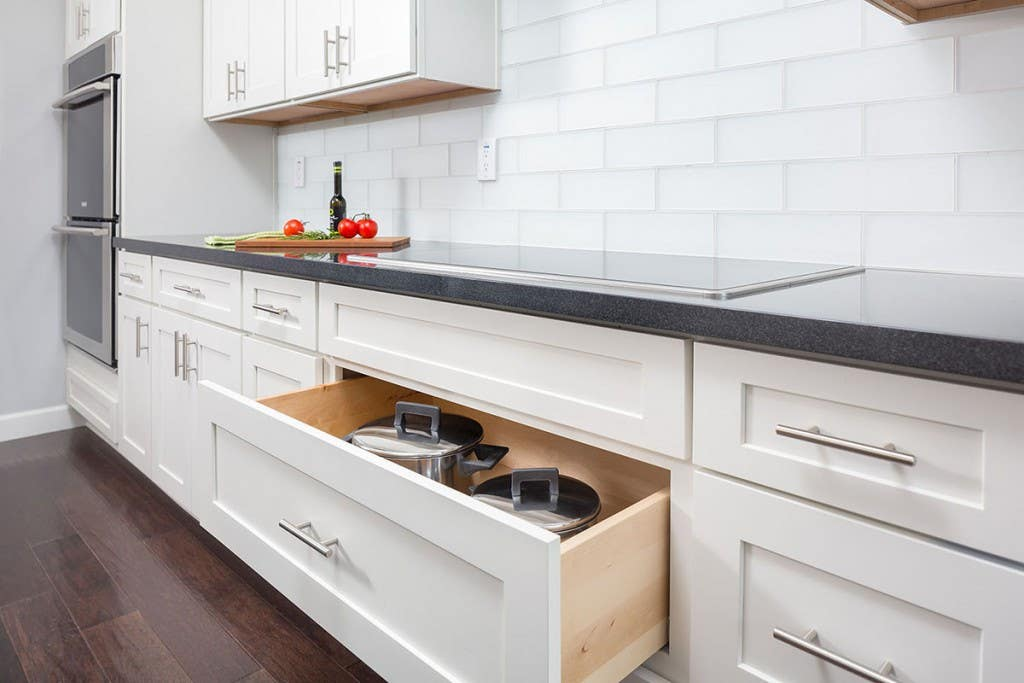 modern kitchen cooktop wall has deep drawer storage, black granite countertops, white shaker cabinets, built in wall ovens and large white glass subway tile backsplash