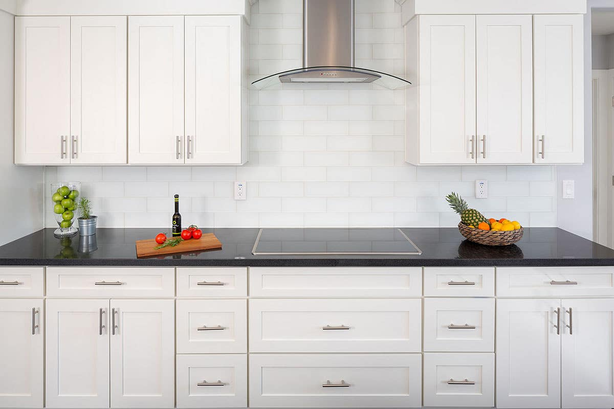 cooktop wall in modern kitchen has recessed panel white painted cabinets, stainless and glass range hood surrounded by base cabinets with short wire pulls