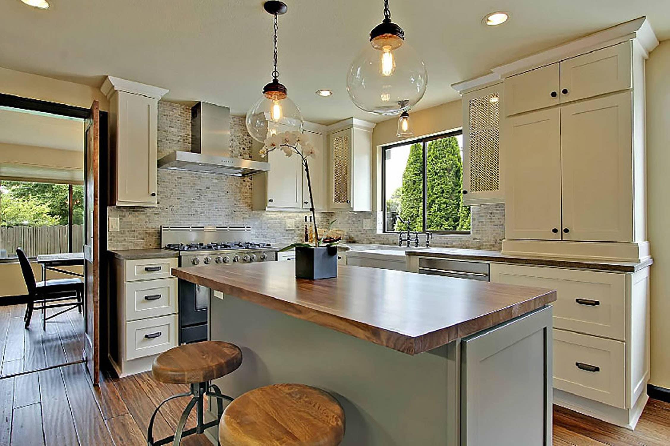 kitchen has white shaker cabinets, wood countertops, bar stools and floor, and natural stone backsplash