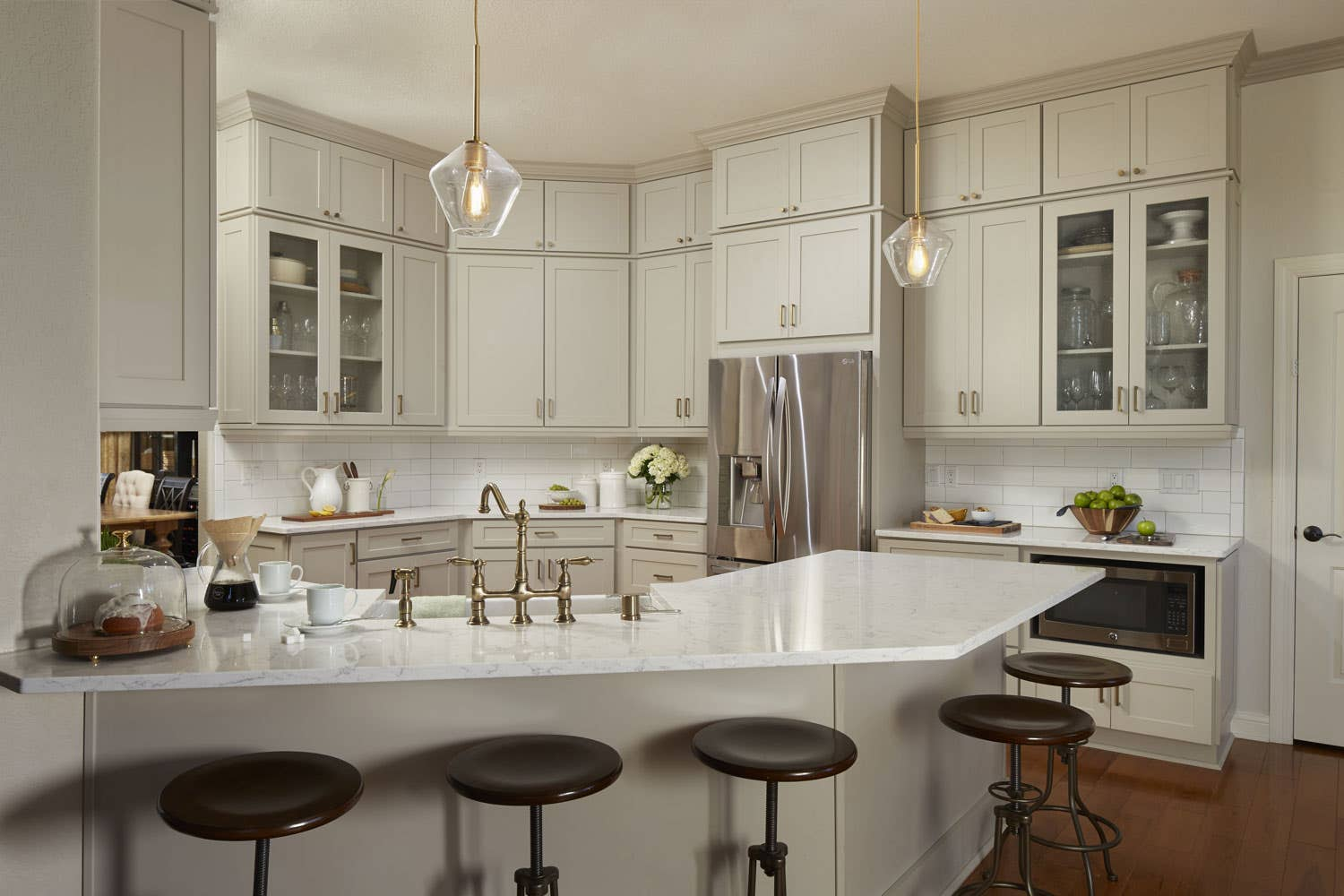 transitional gray kitchen remodeled with white countertops and glass cabinet doors