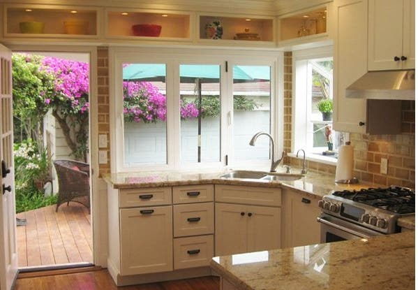 California kitchen with shaker white cabinets has pass-through windows over the sink that open to a patio bar