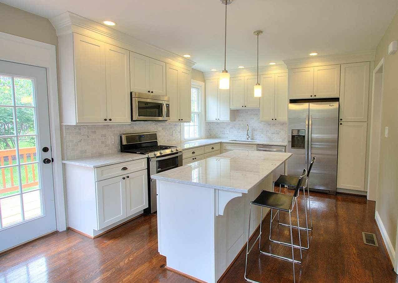 Kitchen has white Shaker cabinets, mullion window and french doors, rich oak hardwood floors and a center island facing the french doors