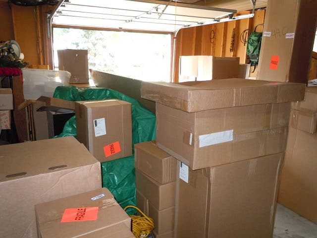 Cabinets in boxes stacked in garage
