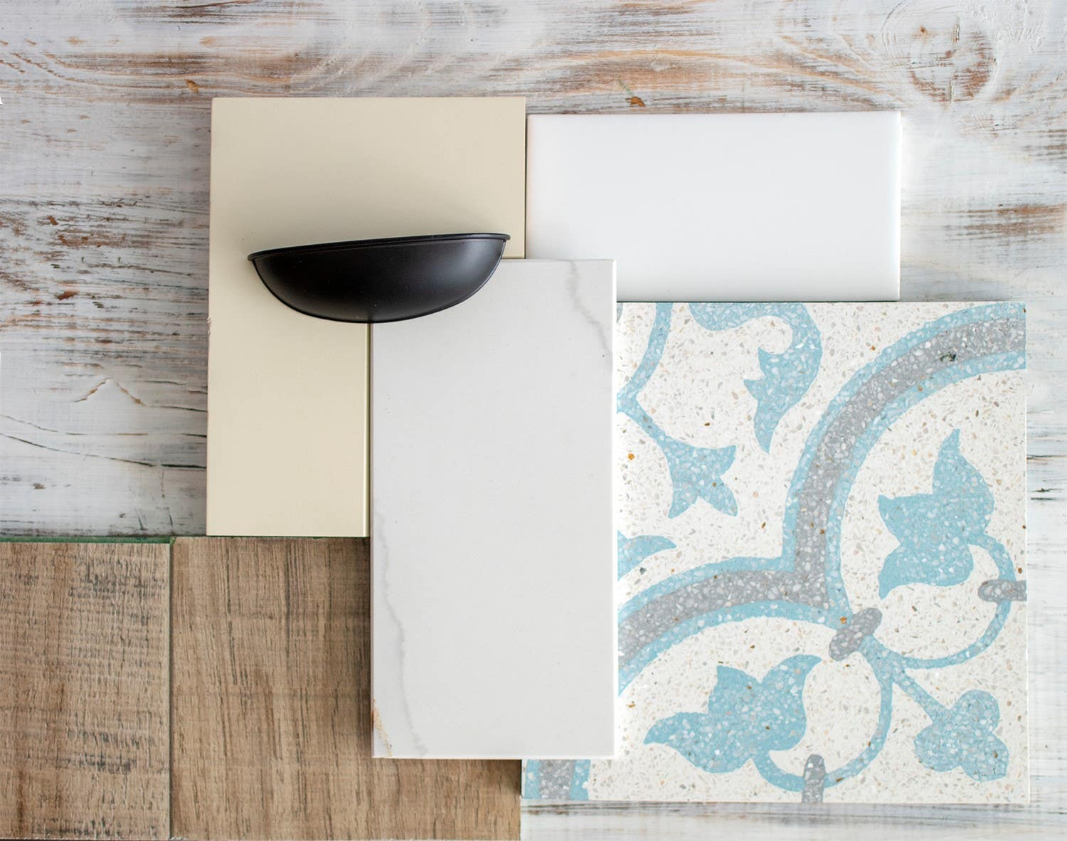 design mood board featuring white tile, black cup pull, white cabinet sample and wood background