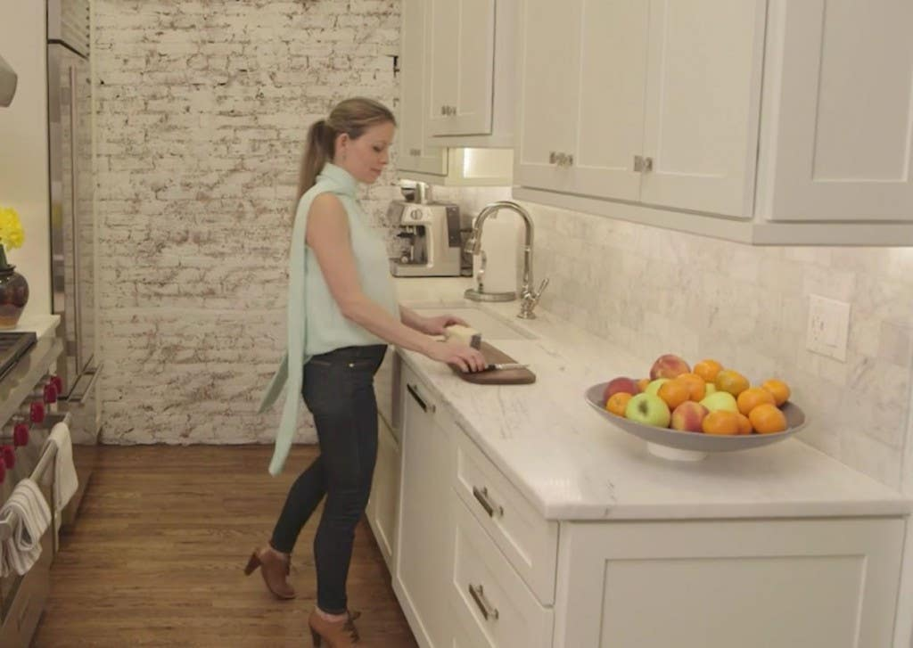 woman in kitchen with white cabinets, white marble countertops and paneled dishwasher cuts fruit