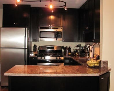 u-shaped kitchen with black cabinets and granite countertop