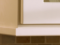 corner of white wall cabinets trimmed with light rail to conceal under-cabinet lighting