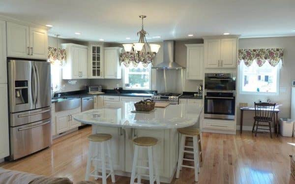 Large kitchen features CliqStudios.com Lyndale raised panel cabinets in painted White finish, seating at a square island