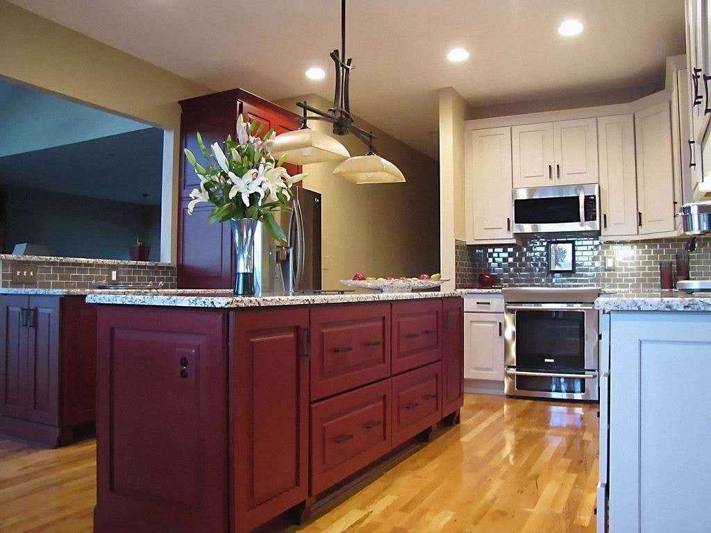 Two-tone kitchen with red center island and white perimeter cabinets in a raised panel cabinet style with gray granite countertops and hardwood flooring