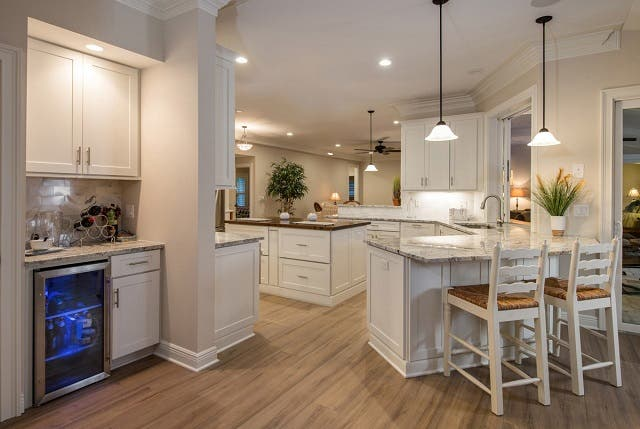 large open kitchen with peninsula, island, bar and look-through wall to living area