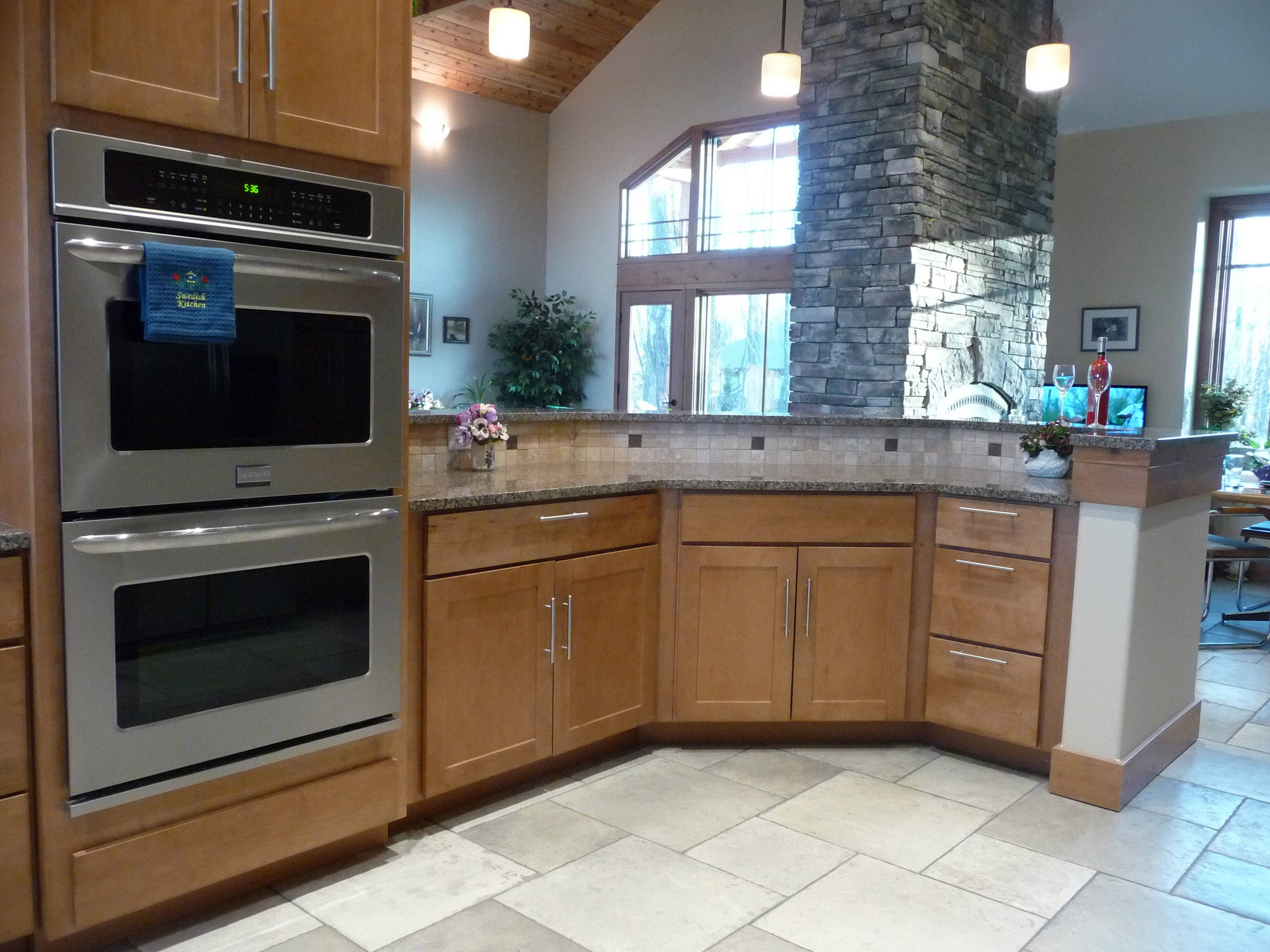 hex kitchen peninsula in maple shaker cabinets adjacent to double wall ovens