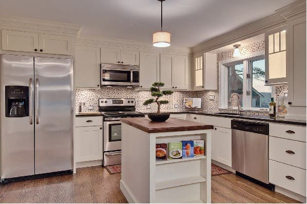 White shaker cabinets in kitchen have stacked crown molding to meet ceiling