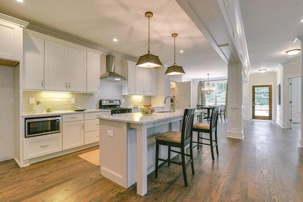 open kitchen features beam and pillar trimmed with board-and-batten look to enhance shaker cabinets in older home