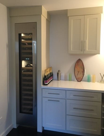 Wine cellar cabinet in butlers pantry with cabinet created from white shaker cabinetry