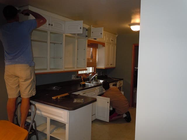 two men removing cabinet doors and disconnecting sink plumbing in kitchen with white cabinets and black countertops