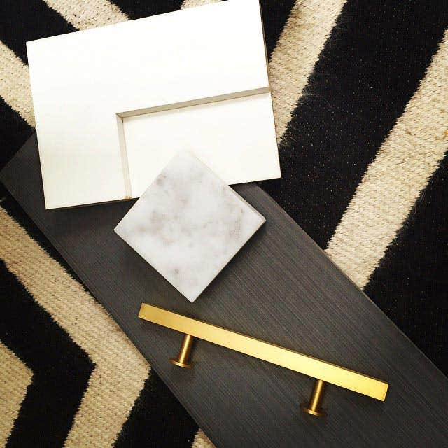 kitchen sample pieces like cabinet and granite samples on a black and white zig-zag rug.