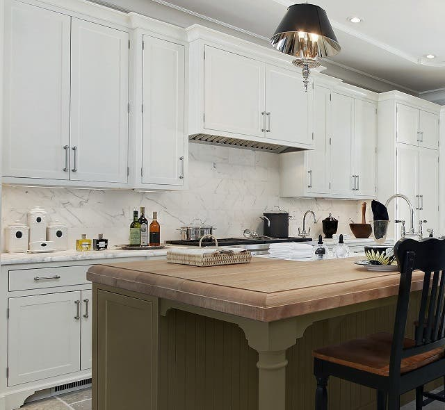 kitchen with white cabinets along the walls and green painted cabinets in the island
