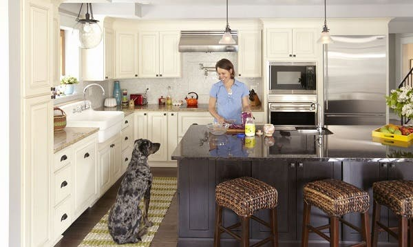 woman cooking at center island smiles at large dog sitting nearby in kitchen with linen raised panel cabinets on perimeter and dark furniture look island